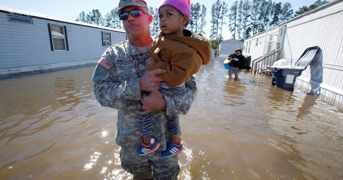 """Боєць Національної гвардії США несе дворічну дівчинку через паводкові води під час операції з порятунку мешканців парку мобільних будинків у місті Ламбертон, яке постраждало внаслідок урагану """"Метью"""". @ Reuters"""