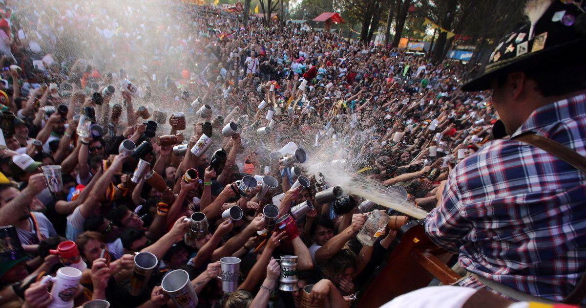 Відвідувачі намагаються заповнити свої кухлики у той час, як пиво розпорошується на них з бочки на Октоберфесті у Вілла Генерал Бельграно, Аргентина. @ Reuters