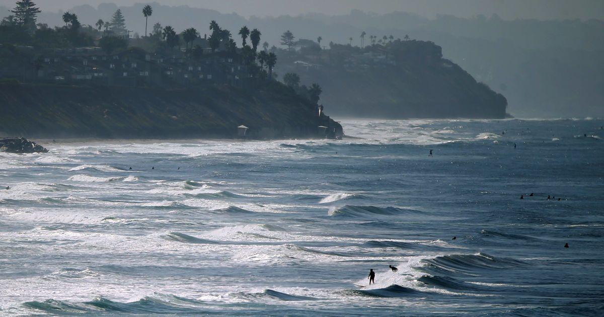 Люди насолоджуються пляжем і хвилями в осінній день уздовж узбережжя в Карлсбаді, штат Каліфорнія, США. @ Reuters