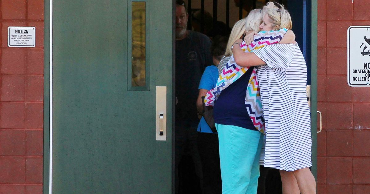 Вчителі обіймають один одного після стрілянини. @ Reuters