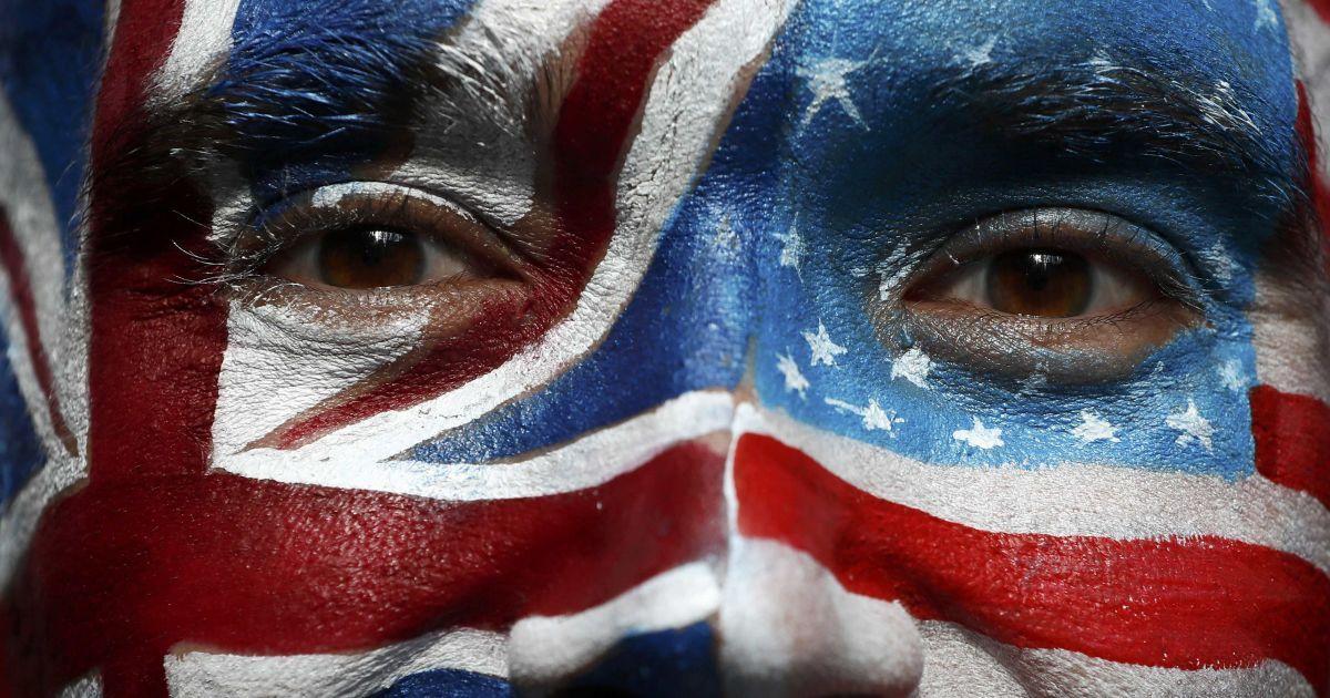"""Чоловік із намальованими на обличчі прапорами Британії та США під час акції """"Стоп Трамп"""" у Лондоні закликає американців, що живуть за кордоном, зареєструватися і проголосувати на майбутніх виборах президента США. @ Reuters"""
