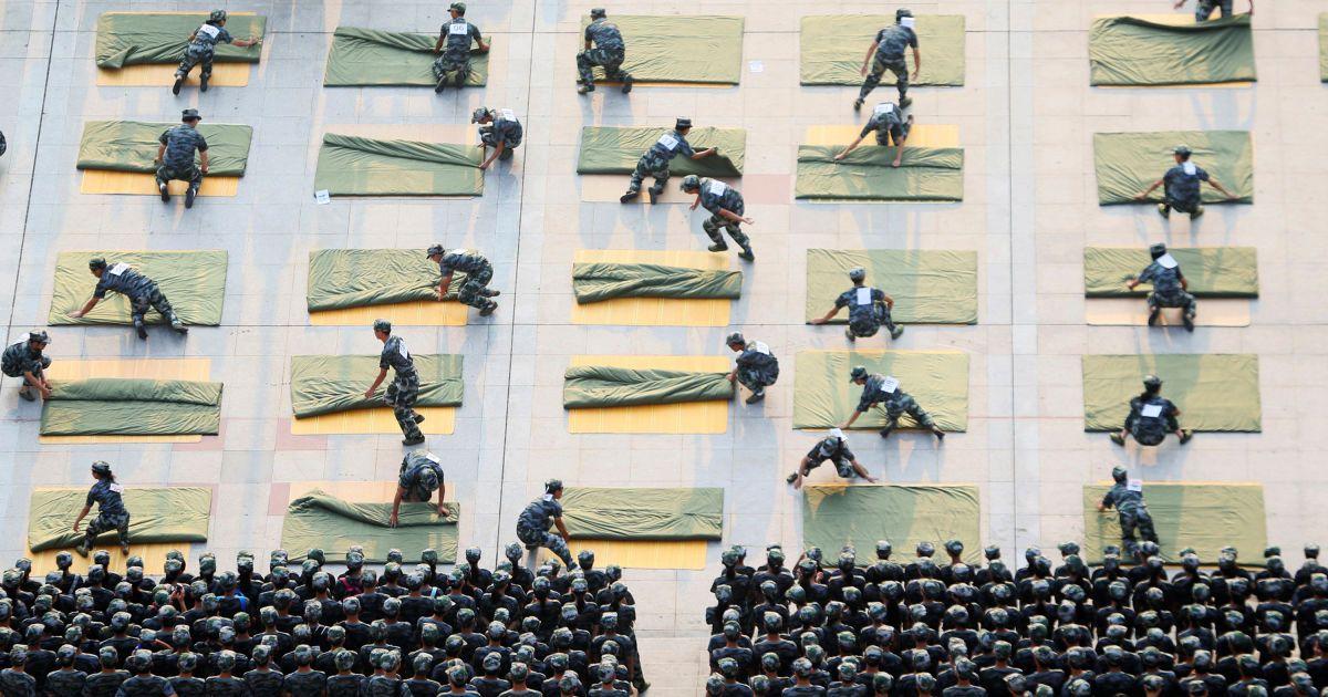 Студенти університету беруть участь у конкурсі зі складання ковдр під час військової підготовки на початку нового семестру у місті Хенян, провінція Хунань, Китай. @ Reuters