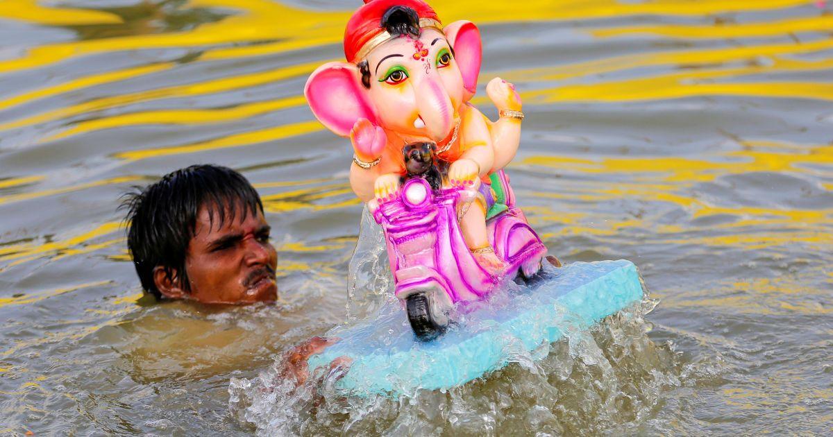 Чоловік занурює ідол індуїстського бога Ганеші, божества процвітання, в ставку на другий день свята Ганеші-Чатуртхі в Ахмадабаді, Індія. @ Reuters