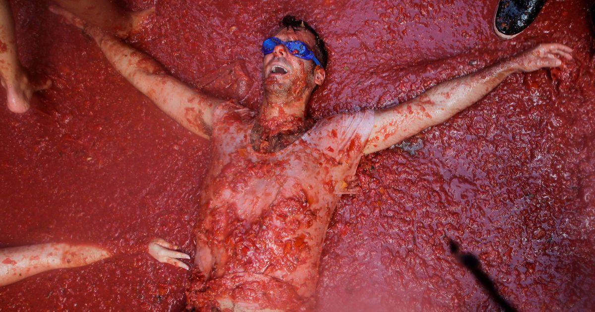 Чоловік лежить у томатній пульпі під час щорічного фестивалю Томатина поблизу Валенсії, Іспанія. @ Reuters
