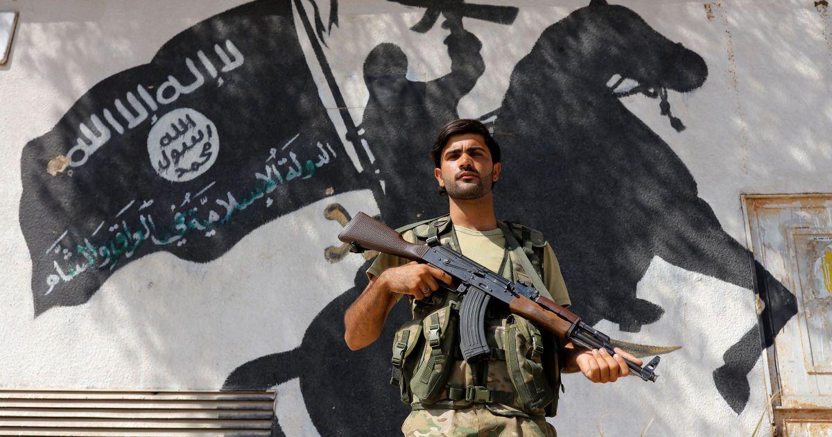 """Член про-турецького угруповання """"Вільна сирійська армія"""" стоїть на тлі муралу бойовиків """"ІД"""" у прикордонному місті Джараблус, Сирія. Турецька армія разом із сирійською опозицію атакувала це місто 24 серпня, вибивши звідти ісламістів. @ Reuters"""