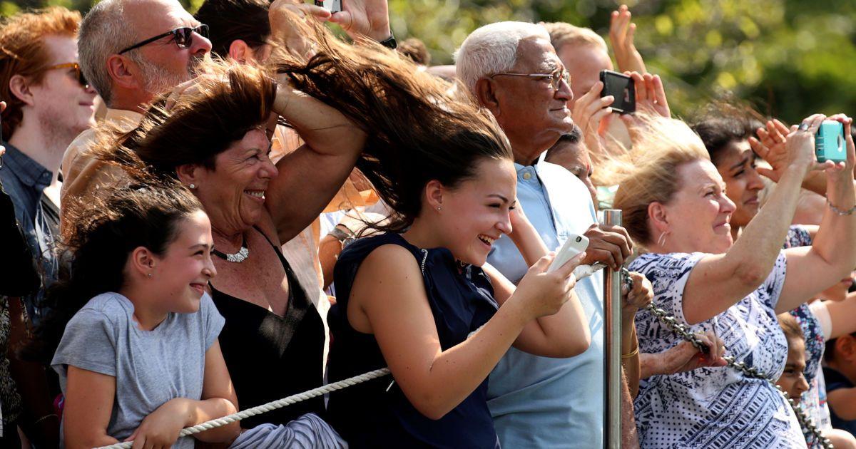 Відвідувачі реагують на вітер від пропелера гелікоптера, яким президент США Барак Обама вирушає з Білого дому у Вашингтоні на шляху до озера Тахо Самміт у Неваді. @ Reuters