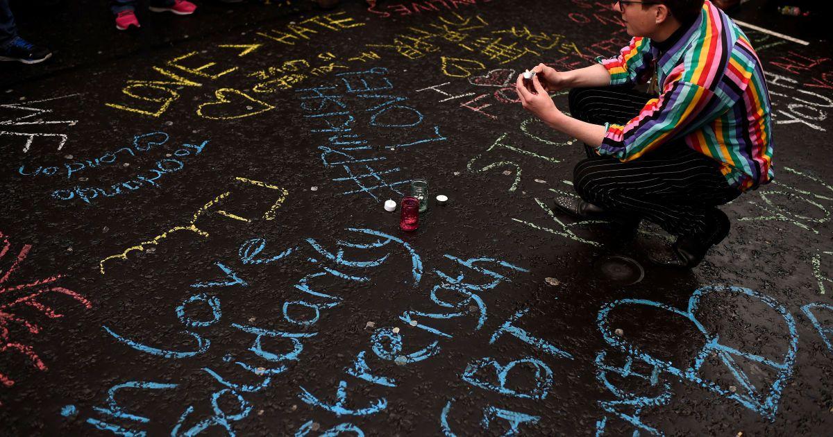 Жінка присідає серед написів на асфальті на честь загиблих у стрілянині в Орландо під час богослужіння в пам'ять про жертв теракту, в районі Сохо в Лондоні. @ Reuters