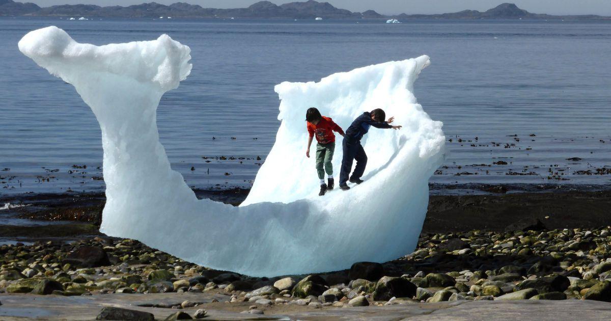 Діти грають серед айсбергів на пляжі в Нууке, Гренландія. @ Reuters