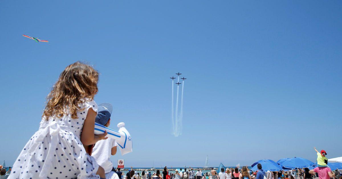 Девочка сидит на плечах у мужчины, наблюдая за воздушным шоу самолетов ВВС Израиля в рамках празднования Дня независимости Израиля по случаю 68-й годовщины создания государства. @ Reuters