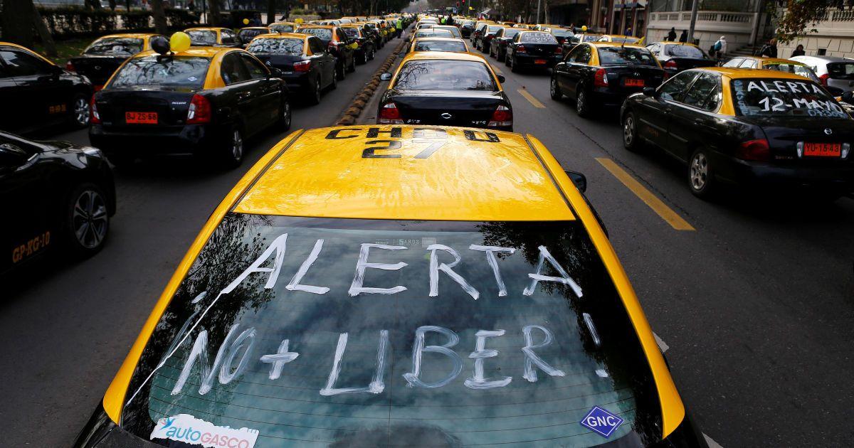 """Такси блокируют улицы во время акции протеста против сервиса такси Uber в Сантьяго, Чили. Надпись на такси говорит: """"Предупреждение. Нет Uber!"""". @ Reuters"""