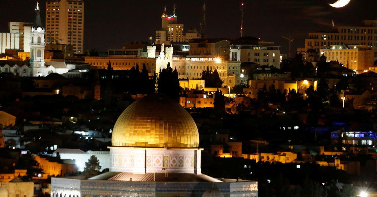 Луна видна над святыней в Иерусалиме, которую мусульмане называют аль-Харам аш-Шариф, а евреи - Храмовой горой. @ Reuters