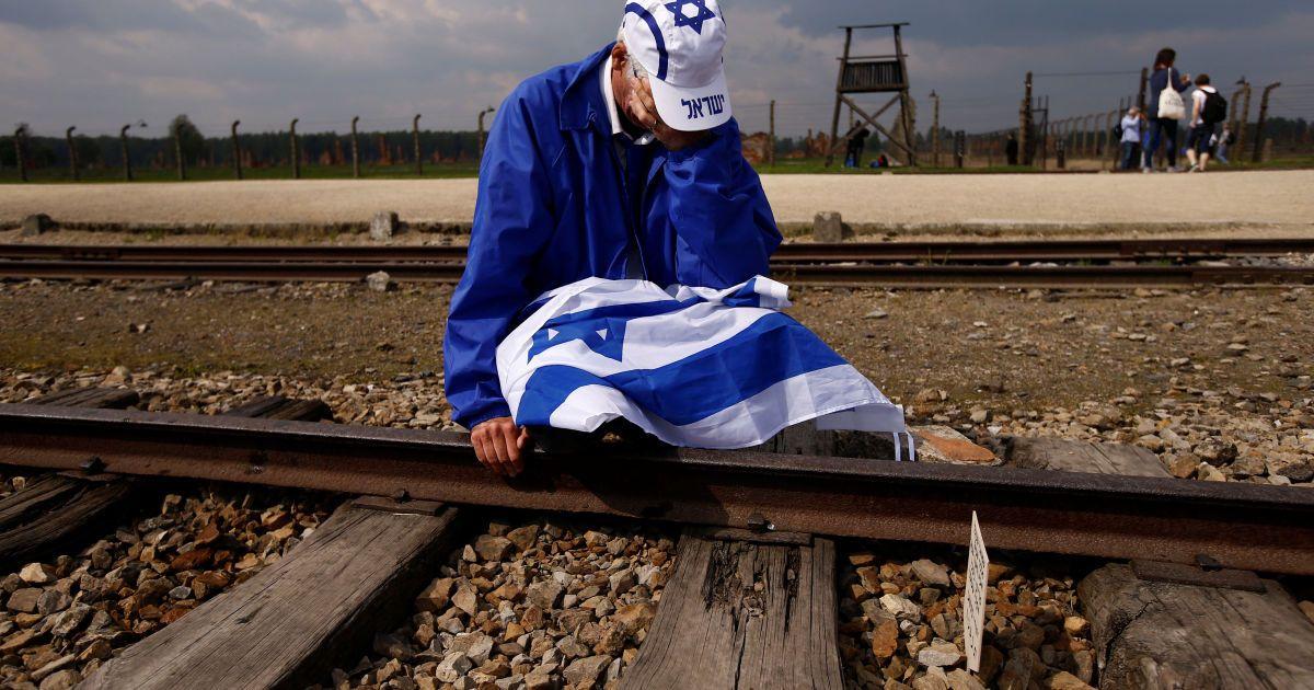 """Чоловік плаче, сидячи на залізничних коліях в колишньому нацистському таборі смерті Освенцим-Біркенау, де тисячі людей з усього світу зібралися на щорічний """"Марш живих"""", щоб вшанувати пам'ять жертв Голокосту. @ Reuters"""