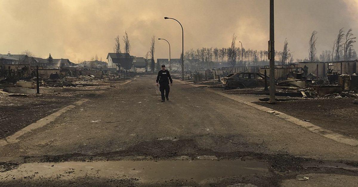 Рятувальник обстежує пошкодження на одній з вулиць у місті Форт Макмюррей,  Канада, яке майже повністю було знищене лісовою пожежею. @ Reuters