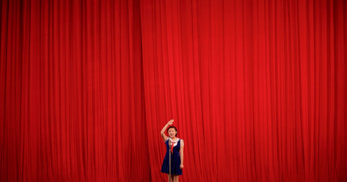 Дівчина віддає честь відвідувачам концерту в дитячому палаці в центрі Пхеньяна, Північна Корея. Місцеві школярі виступили перед делегаціями іноземних журналістів і туристів напередодні сьомого з'їзду Трудової партії Кореї. @ Reuters