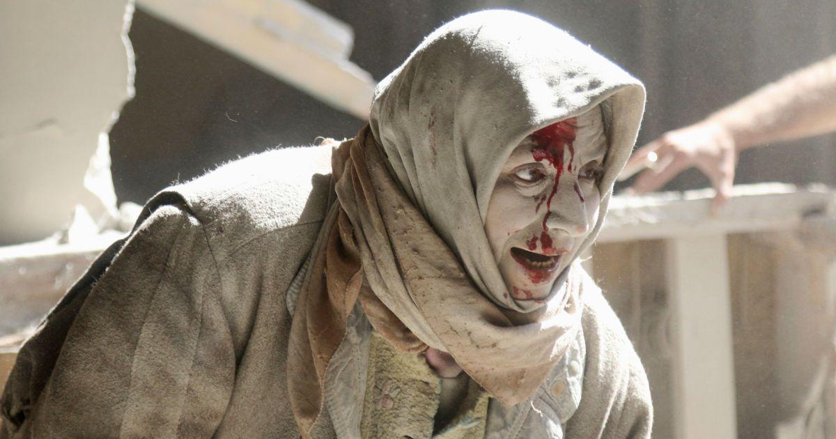 Поранена жінка йде по району сирійського Алеппо, який контролюють повстанці, після авіаудару. @ Reuters