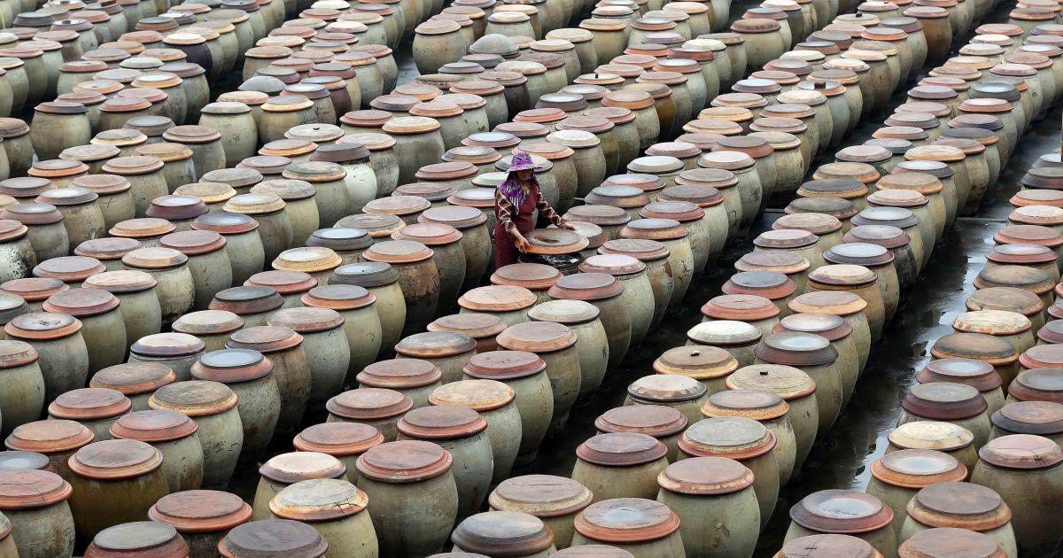 Жінка працює на заводі з використанням традиційного методу для виробництва соєвого соусу в місті Чжинчжан, Китай. @ Reuters