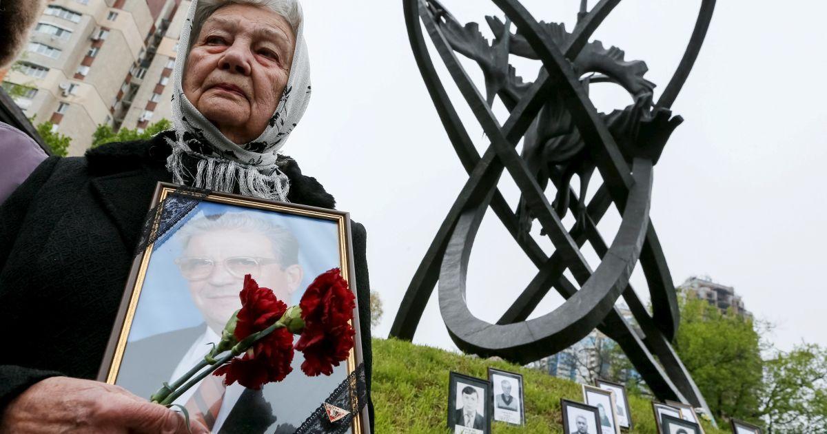 Жінка тримає портрет її родича, жертви аварії на Чорнобильській АЕС, під час церемонії в Києві. @ Reuters