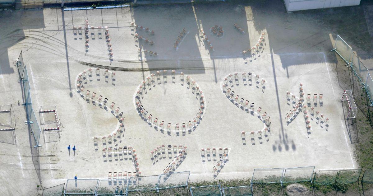 """Слова із стільців, які читаються як """"(Туалет) Папір, хліб, вода і SOS"""", на дитячому майданчику середньої школи після землетрусу в Кумамото на півдні Японії. @ Reuters"""