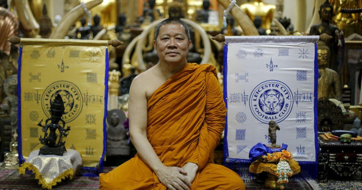 """Буддійський монах позує для фото поруч зі святими полотнами з логотипом англійського футбольного клубу """"Лестер Сіті"""". Монах благословив команду у своєму храмі в Бангкоку, Таїланд. @ Reuters"""
