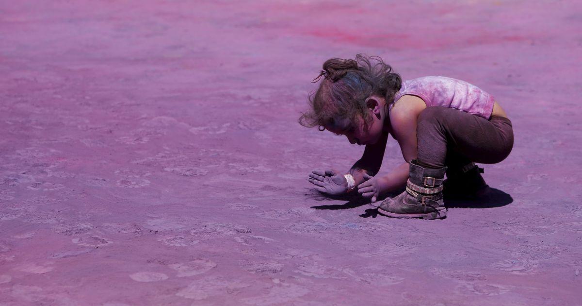 Дитина черпає кольоровий порошок із землі під час свята Холі, організованого мальтійської-індійською громади у Квормі, за межами Ла-Валлетти, Мальта. @ Reuters