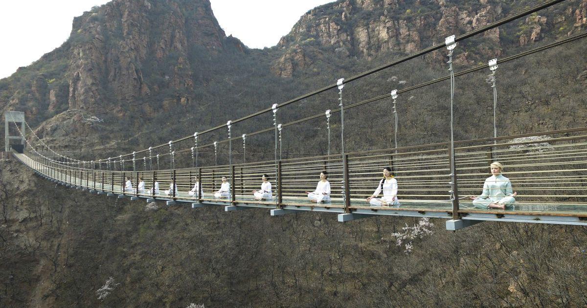 Жінки виконують йогу на скляному підвісному мості - це один із способів залучення туристоів у Чженчжоу, провінція Хенань, Китай. @ Reuters