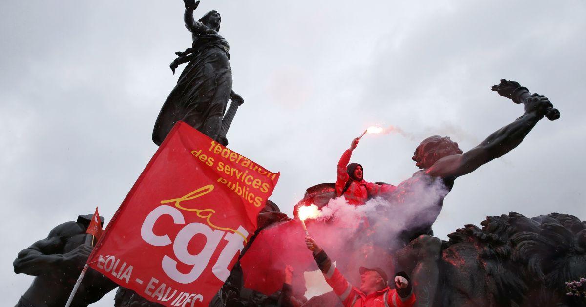 Активісти робітничих профспілок тримають факели безпеки, стоячи  на статуї на Площі нації у Парижі під час демонстрації проти змін трудового законодавства у Франції. @ Reuters