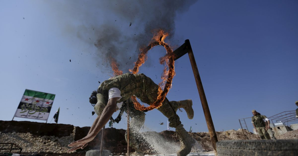 Бойовик сирійської опозиції стрибає через петлю вогню, демонструючи свою майстерність під час військового вишколу в таборі на півночі провінції Хама, Сирія. @ Reuters
