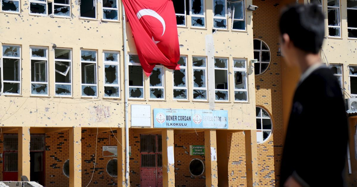 Хлопчик стоїть перед початковою школою, яка була пошкоджена під час операцій із забезпечення безпеки під час зіткнень між турецькими силами безпеки і курдськими бойовиками, в південно-східній частині міста Іділ, Туреччина. @ Reuters