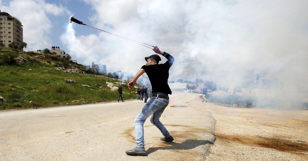 Палестинський демонстрант використовує строп для запуску балончика зі сльозоточивим газом під час зіткнень в знак протесту з нагоди Дня Землі біля міста Рамалла на Західному березі. 30 березня відзначається День землі, щорічне святкування протестів в 1976 році проти присвоєння Ізраїлю арабських земель у Галілеї. @ Reuters