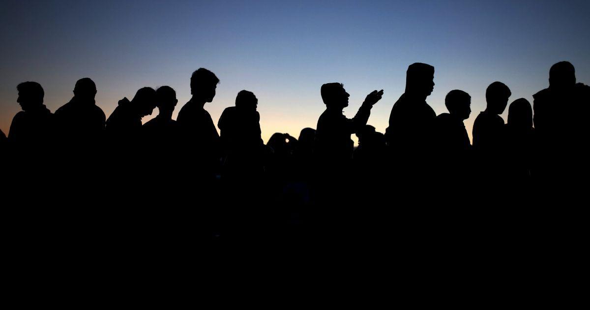 Мігранти та біженці стоять в черзі за їжею в імпровізованому таборі в греко-македонському кордоні поблизу села Ідоменей, Греція. @ Reuters