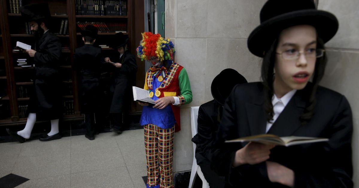 Ультраортодоксальний єврейський хлопчик, одягнений в костюм клоуна, бере участь в читанні книги Естер під час святкування єврейського свята Пурим. Під час цього свята євреї відзначають річницю порятунку від геноциду в стародавній Персії. @ Reuters