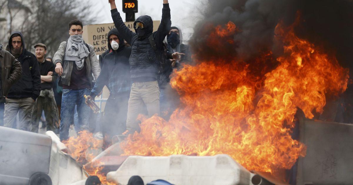 Демонстранти стоять поблизу палаючого сміття під час акції протесту французьких студентів середніх шкіл і університетів проти законопроекту про реформу праці у Франції. @ Reuters