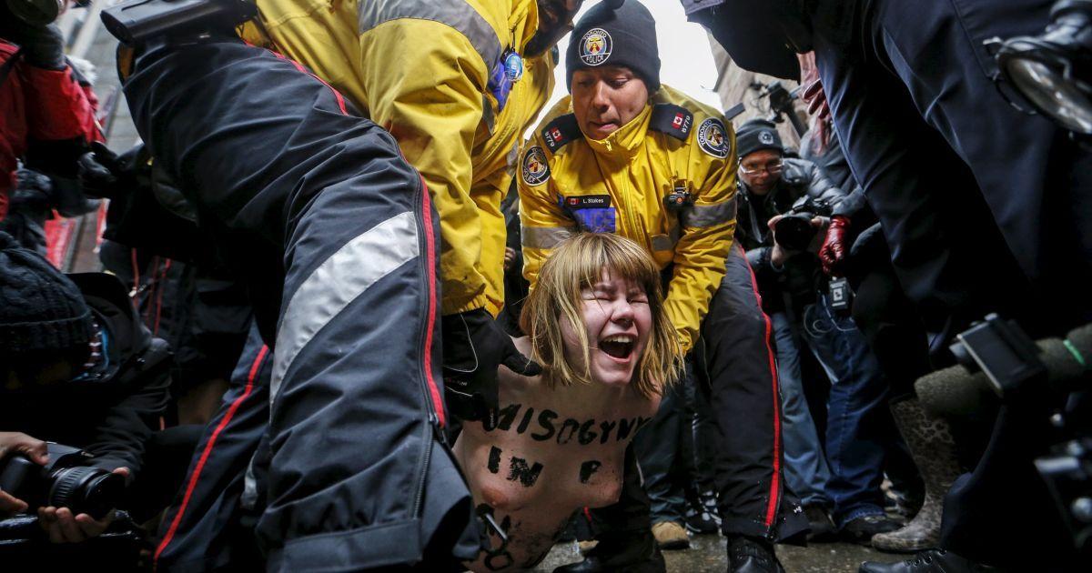 Оголена топлес протестувальниця затримується поліцією під час акції протесту проти рішення судді Онтаріо, який визнав колишнього власника канадського радіо Цзянь Гомеші невинним за чотирма звинуваченнями у сексуальному насильстві. @ Reuters
