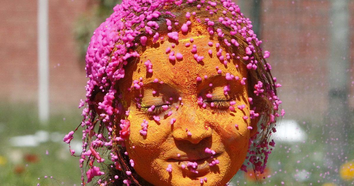 Студентка із змащеним кольоровим порошком обличчям святкує Холі в університетському містечку в місті Чандігарх, Індія. @ Reuters