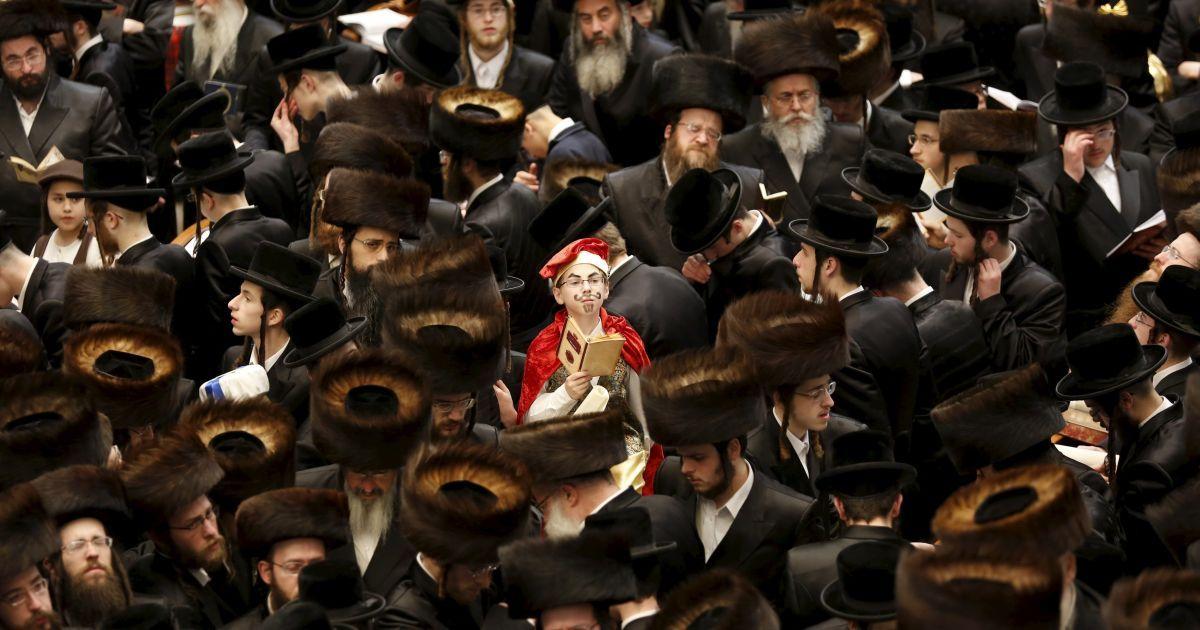 Ультраортодоксальний єврейський хлопчик з хасидської династії Белз, одягнений в червоний костюм, бере участь в читанні з книги Естер під час єврейського свята Пурим. Євреї відзначають це свято на згадку про порятунок цього народу від геноциду у стародавній Персії. @ Reuters
