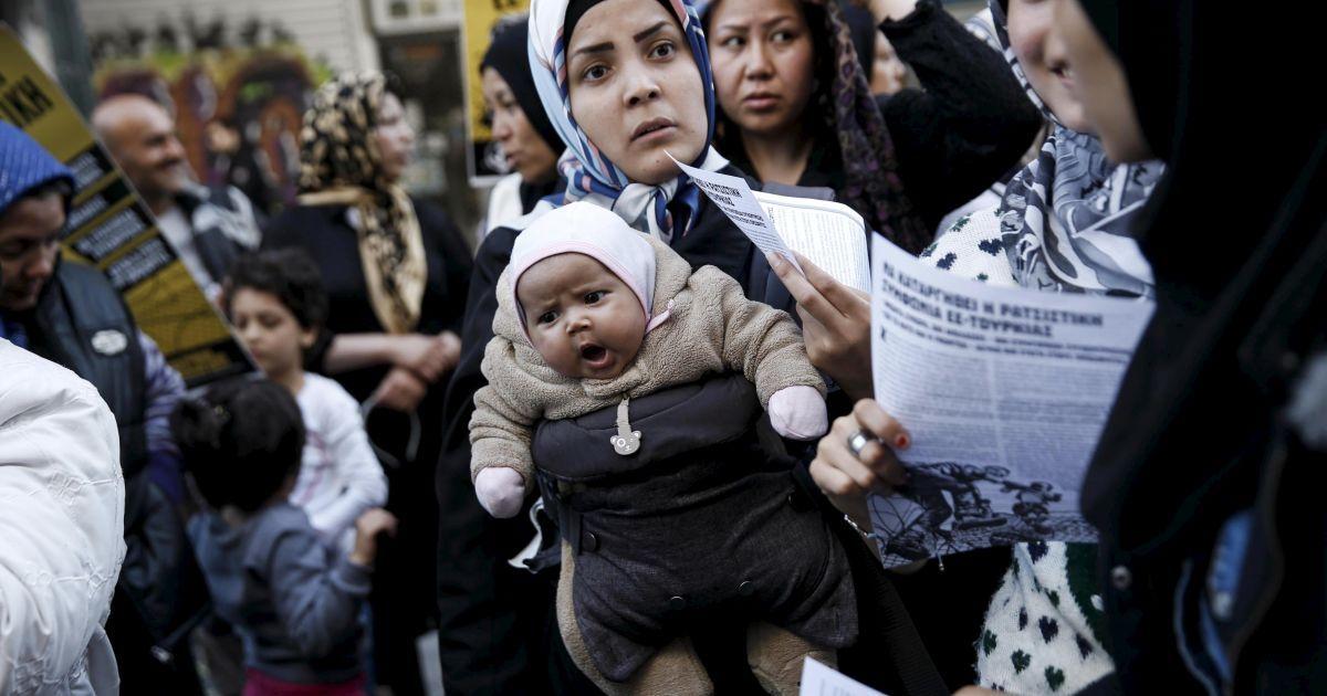 Афганська мігрантка несе свою дитину поряд з активістами і студентами, які беруть участь в акції протесту проти недавнього закриття кордону через Балкани, в Афінах, Греція. @ Reuters