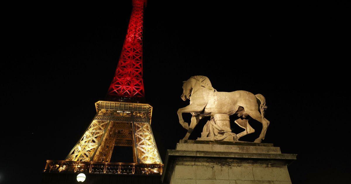 Ейфелева вежа у Парижі світиться кольорами бельгійського прапору.
