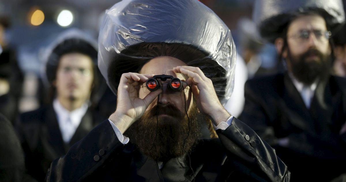Ультраортодоксальний єврей використовує бінокль під час весільної церемонії онука раббі Йосефа Дов Моше Хальберштама, релігійного лідер хасидської династії Санс, і онукою релігійного лідера Толдот Авраама Іцхака, в Нетанії, Ізраїль. @ Reuters