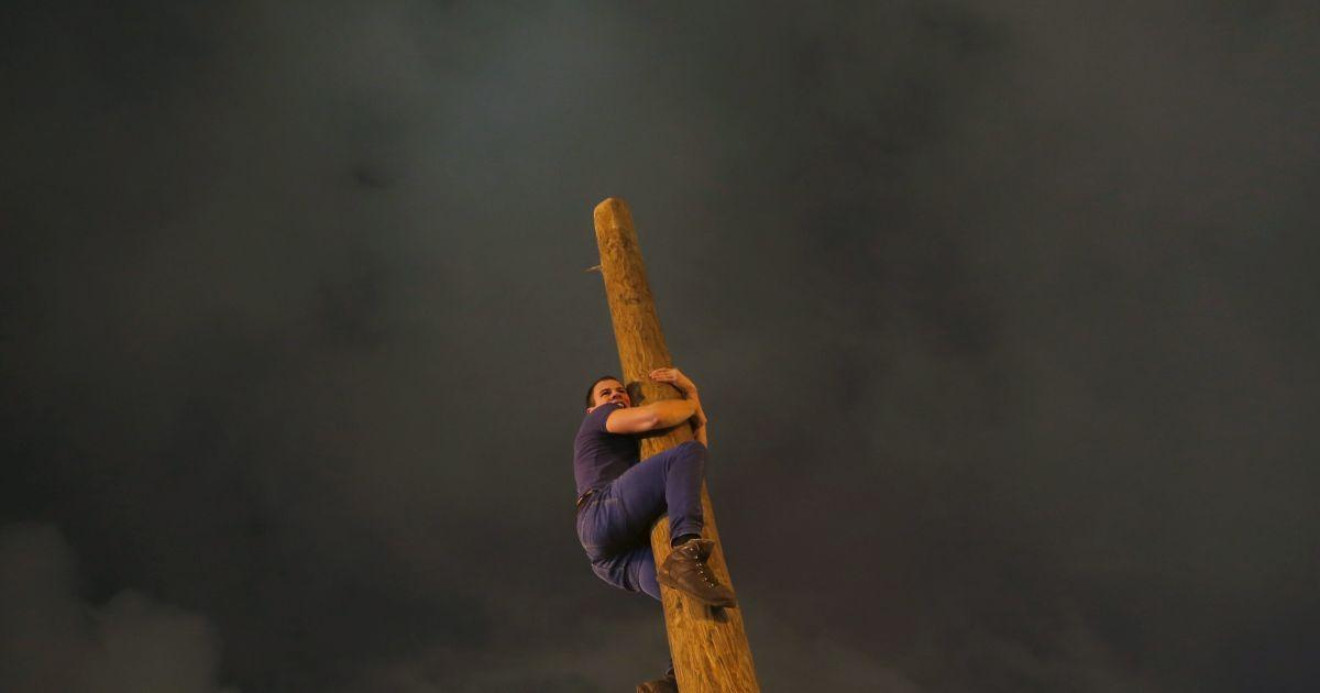 Людина піднімається вгору по дерев'яному стовпу під час святкування Масляни у парку Горького в Москві, Росія. @ Reuters