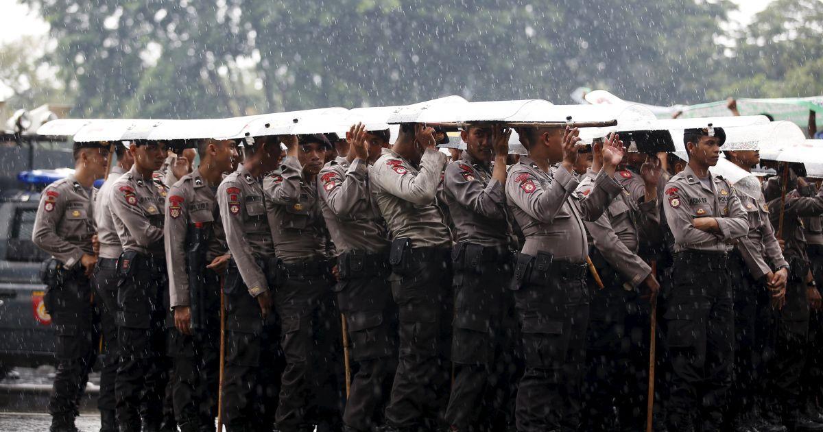 Поліція використовує щити, щоб сховатися від дощу під час акції протесту з боку водіїв таксі за межами президентського палацу в Джакарті, Індонезія. @ Reuters