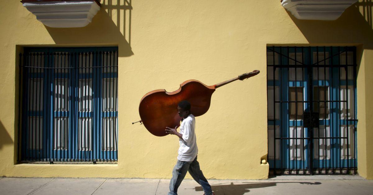 Музикант несе контрабас в центрі міста Гавана, Куба. @ Reuters
