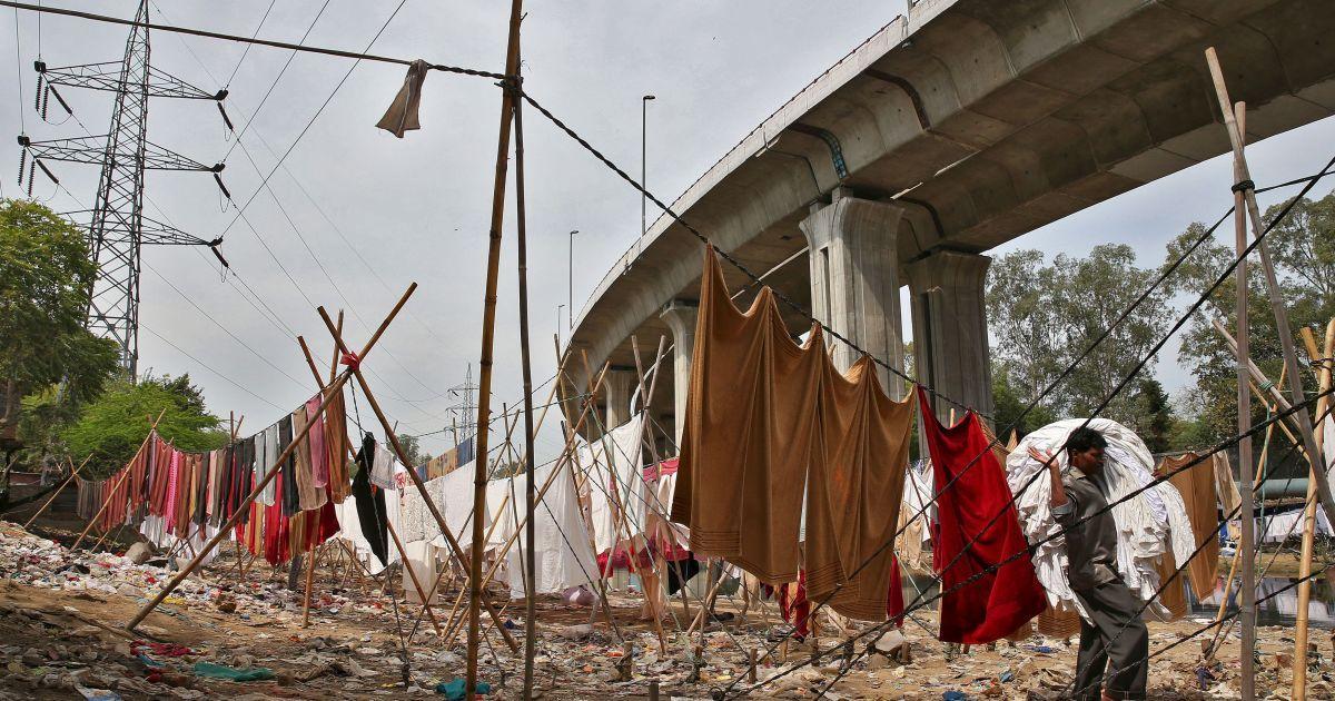 Мийник збирає білизну під мостом у Нью-Делі, Індія. @ Reuters