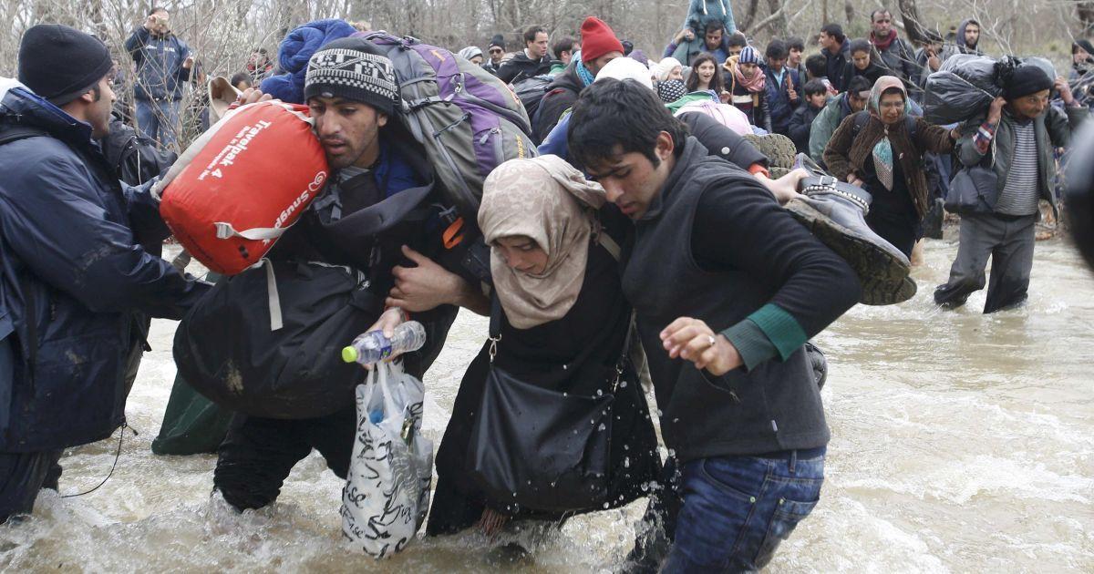 Мігранти йдуть вбрід через річку поруч з греко-македонським кордоном, на захід від села Ідоменей, Греція. 14 березня сотні мігрантів прорвалися на територію Македонії. @ Reuters