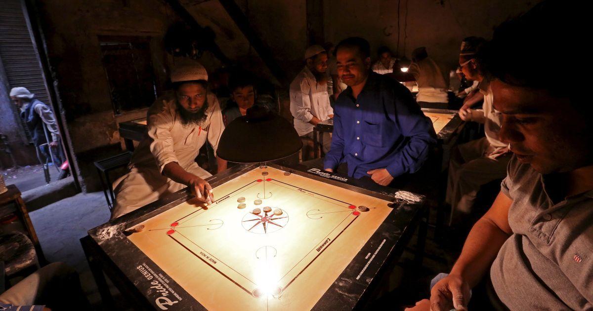 Чоловіки грають в гру Карром в нелегальній будівлі в районі Старого Делі, Індія. @ Reuters