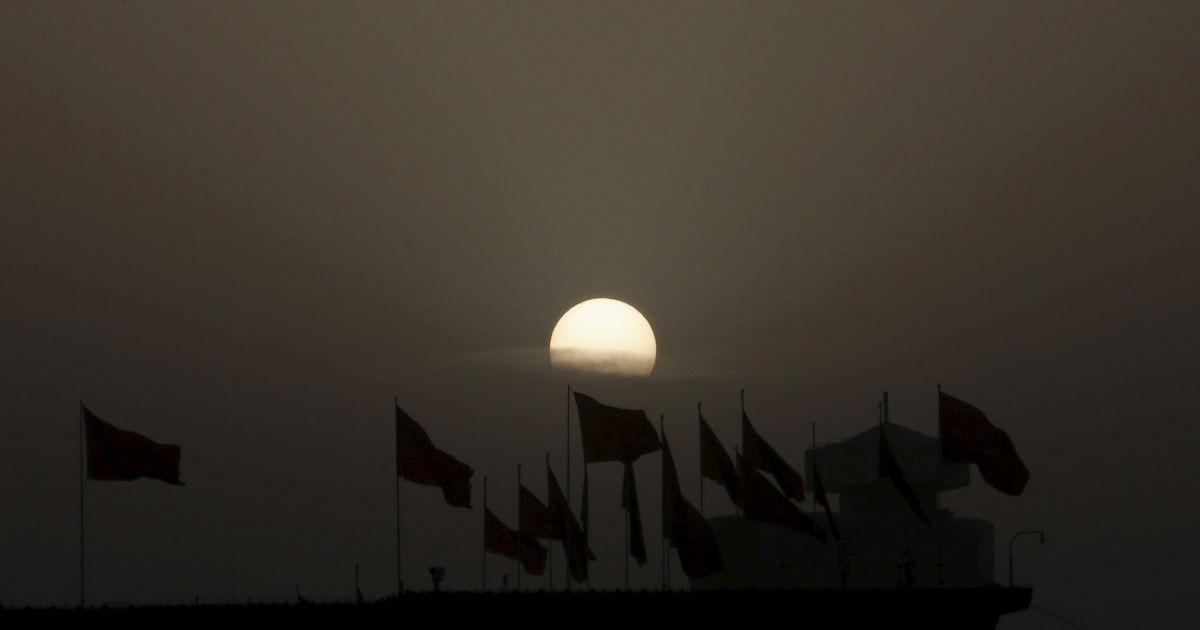 Сонце піднімається над червоними прапорами на даху флатера Національного музею на площі Тяньаньмень перед відкриттям сесії Всекитайських зборів народних представників в Пекіні, Китай. @ Reuters
