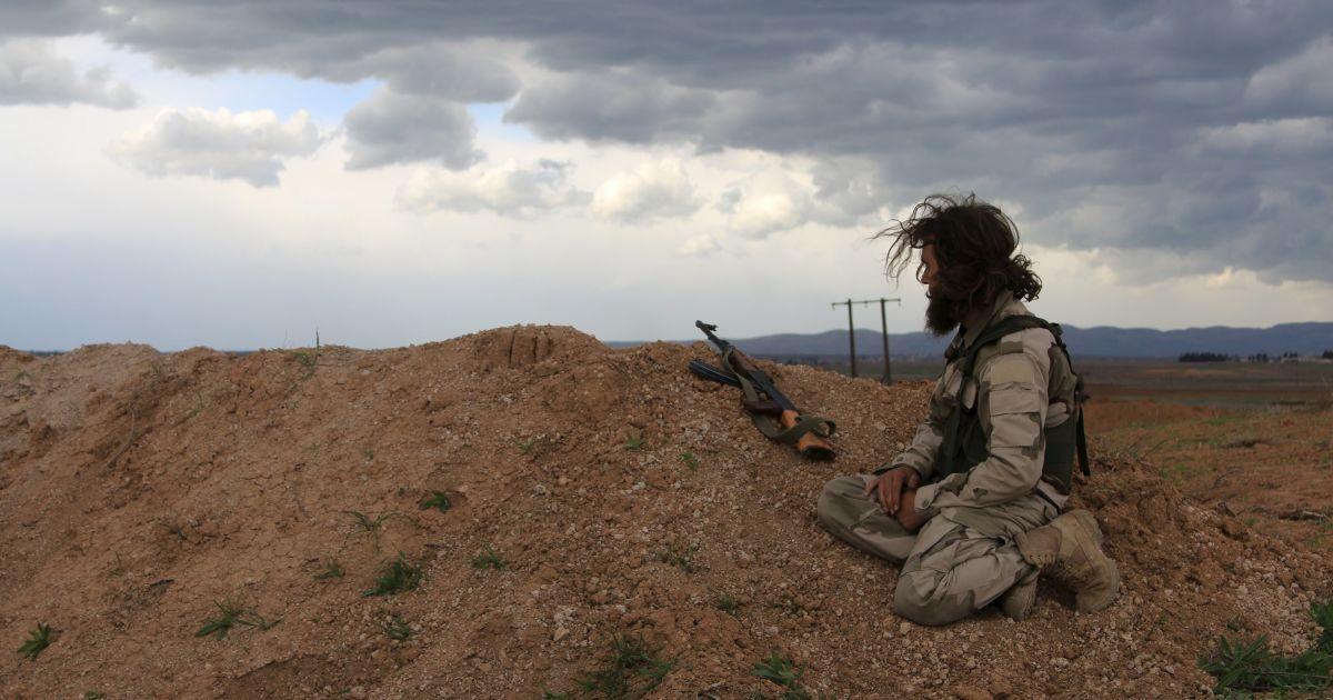 Бойовик сирійської опозиції сидить на точці спостереження зі своєю зброєю в селі Аль-Латамна у Сирії. @ Reuters