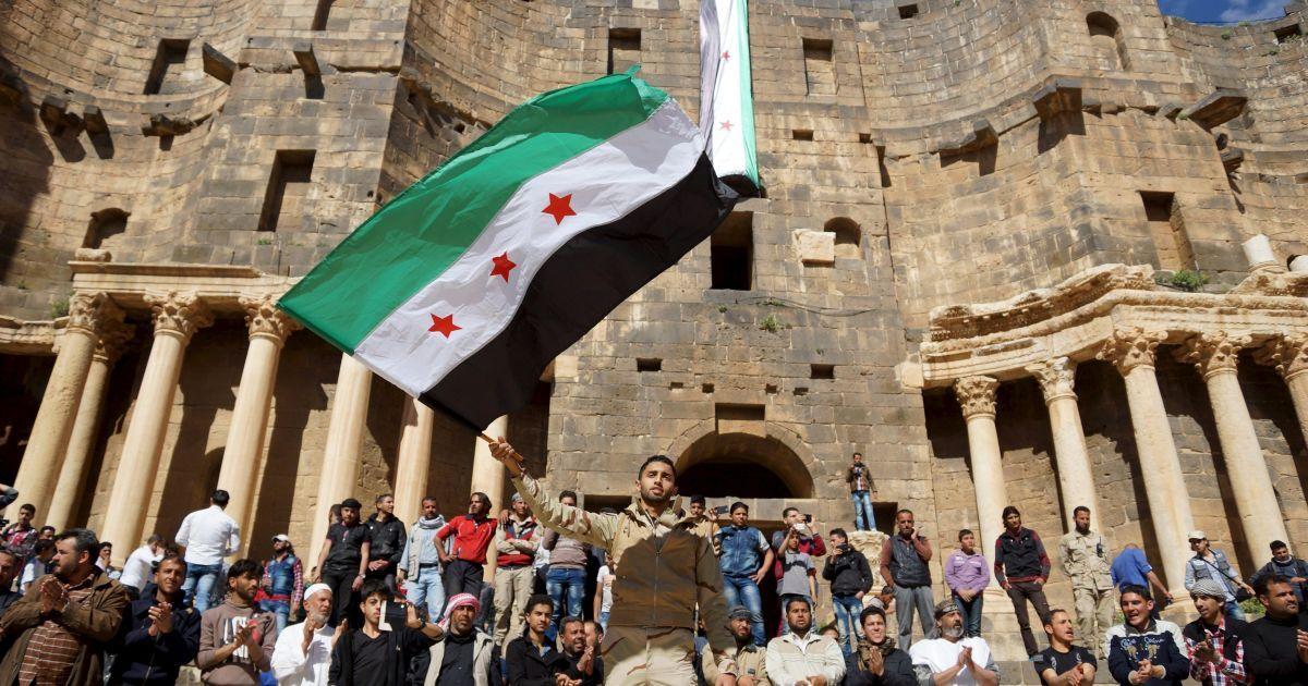 Протестувальник тримає прапор сирійської опозиції під час антиурядової акції протесту всередині римського амфітеатру другого століття в історичному сирійському південному місті Босра аль-Шам. @ Reuters