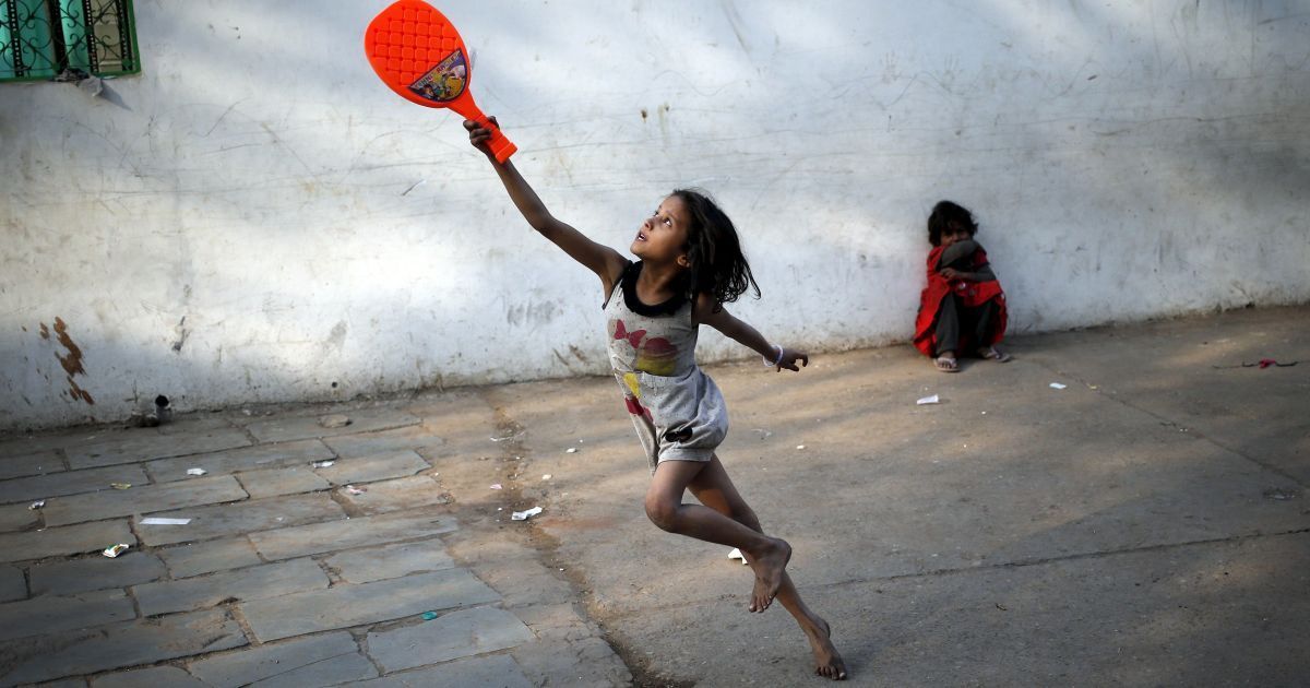 Дитина грає з пластиковою ракеткою для бадмінтону в старих кварталах Делі, Індія. @ Reuters