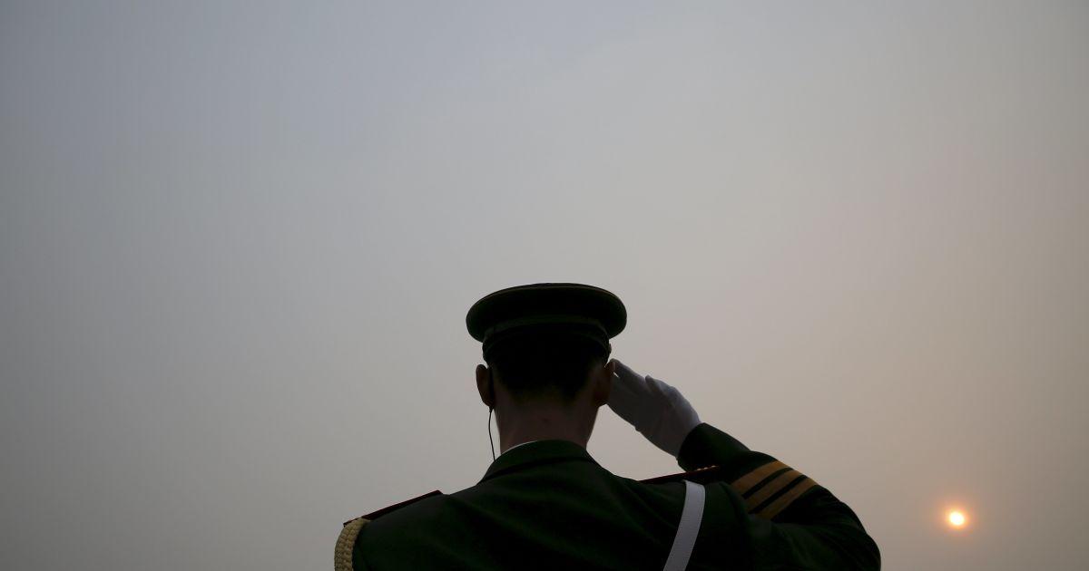 Сонце видно через смог у сильно забруднений день у той час, як поліцейський салютує делегатам, які прибувають до Великого залу народів напередодні суботньої церемонії відкриття Національного народного конгресу у Пекіні, Китай. @ Reuters