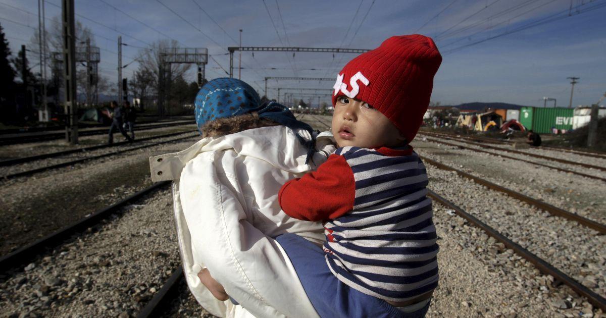 Мігрант несе дитину по дорозі до імпровізованого табору для біженців на греко-македонському кордоні, недалеко від села Ідоменей, Греція. @ Reuters